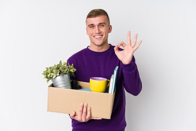 Młody kaukaski mężczyzna przenosi się do nowego domu, wesoły i pewny siebie, pokazując ok gest.