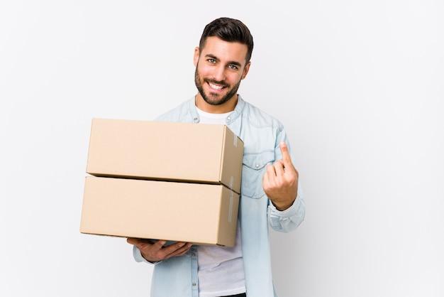 Młody kaukaski mężczyzna przeprowadzka do nowego domu na białym tle, wskazując palcem na ciebie, jakby zapraszając podejść bliżej.