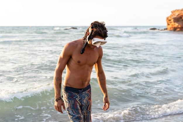 Młody kaukaski mężczyzna przygotowuje się do nurkowania w morzu