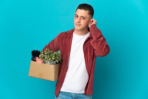 Młody kaukaski mężczyzna robi ruch podczas podnoszenia pudełka
