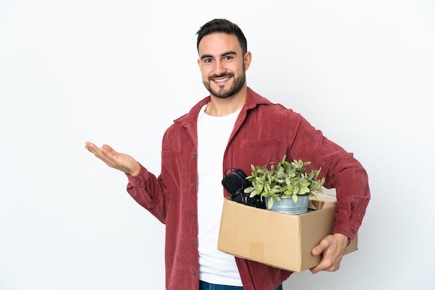 Młody kaukaski mężczyzna robi ruch, podnosząc pudełko pełne rzeczy na białej ścianie wyciągając ręce na bok, by zaprosić do przyjścia