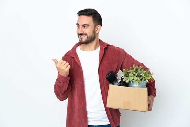 Młody kaukaski mężczyzna robi ruch podnosząc pudełko pełne rzeczy na białym tle wskazując na bok, aby przedstawić produkt