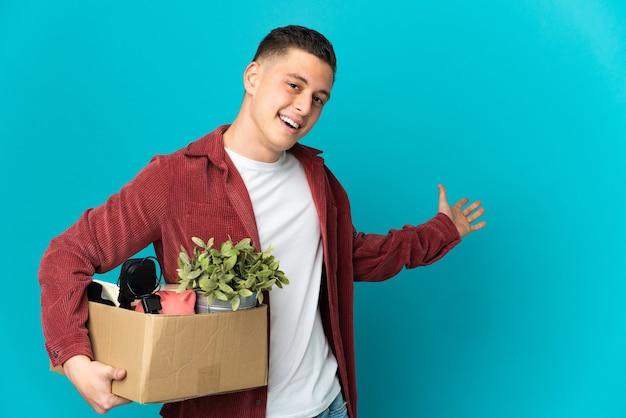 Młody kaukaski mężczyzna robi ruch, podnosząc pudełko pełne rzeczy na niebieskiej ścianie wyciągając ręce na bok, by zaprosić do przyjścia