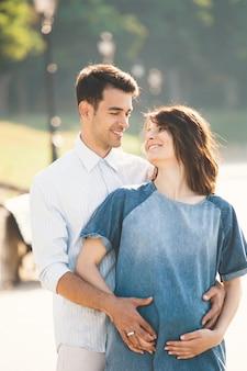 Młody kaukaski mężczyzna ściska ciężarnej żony
