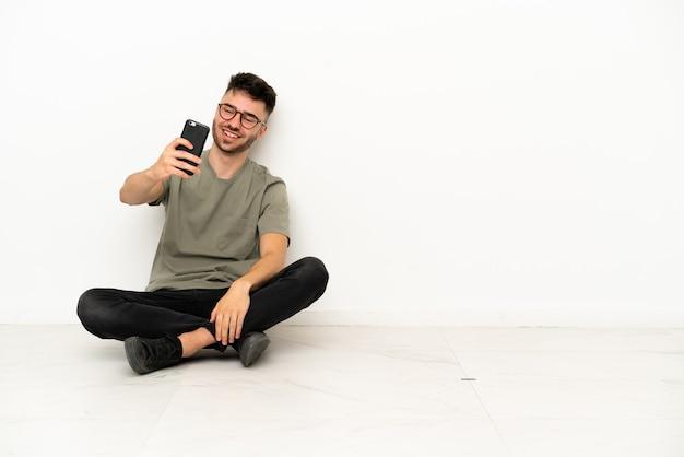 Młody kaukaski mężczyzna siedzący na podłodze na białym tle robi selfie
