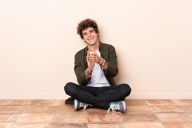 Młody kaukaski mężczyzna siedzi na podłodze, brawo po prezentacji na konferencji