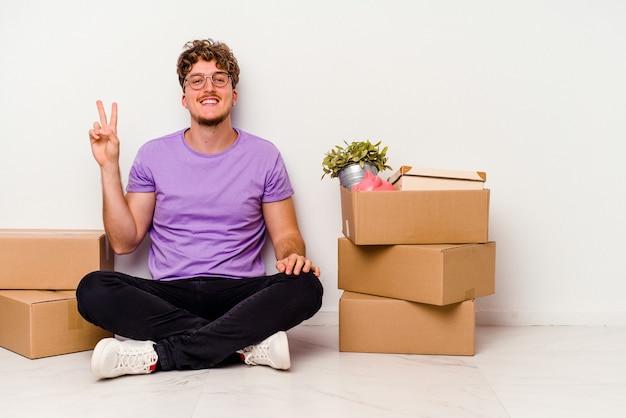 Młody kaukaski mężczyzna siedzi na podłodze gotowy do poruszania się na białym tle na białym tle radosny i beztroski pokazując palcem symbol pokoju.
