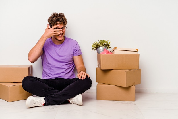 Młody kaukaski mężczyzna siedzi na podłodze gotowy do ruchu na białym tle na białym tle mruga do aparatu palcami, zawstydzony zakrywający twarz.