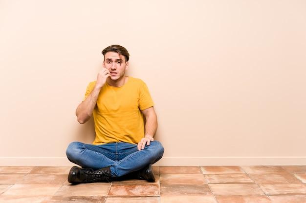 Młody kaukaski mężczyzna siedzi na podłodze na białym tle gryząc paznokcie, nerwowy i bardzo niespokojny.