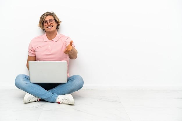 Młody kaukaski mężczyzna siedzi na podłodze z laptopem na białym tle, ściskając ręce za zamknięcie dużo