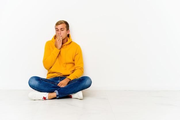 Młody kaukaski mężczyzna siedzi na podłodze ziewając, pokazując zmęczony gest obejmujący usta ręką.