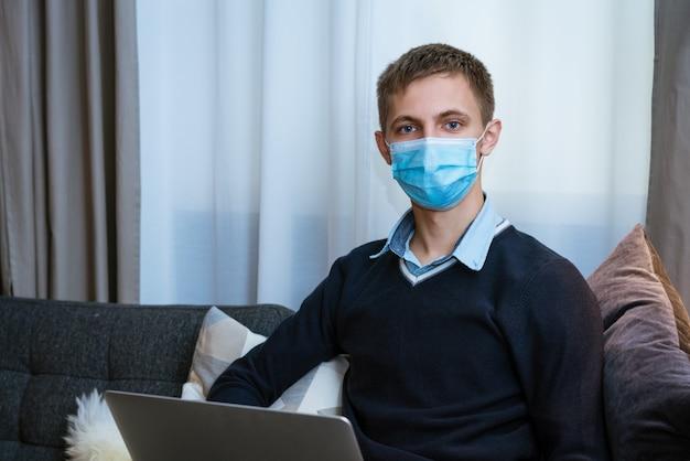 Młody kaukaski mężczyzna siedzi w domu na kanapie z laptopem w masce medycznej
