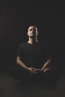 Młody kaukaski mężczyzna siedzi w medytacji z czarnych ubrań i czerni