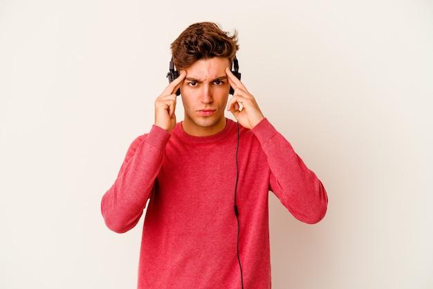 Młody kaukaski mężczyzna słucha muzyki na białej ścianie, koncentruje się na zadaniu, trzymając wskazujące głowę palce.