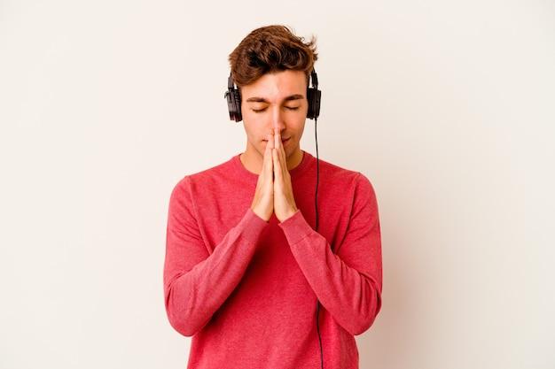 Młody kaukaski mężczyzna słucha muzyki na białym tle na białej ścianie, trzymając się za ręce w modlitwie w pobliżu ust, czuje się pewnie.