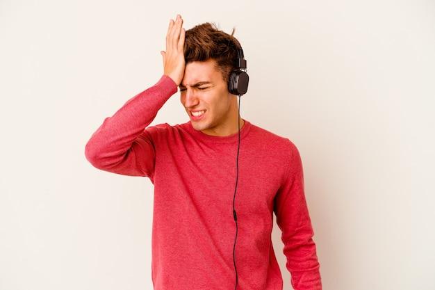 Młody kaukaski mężczyzna słucha muzyki na białym tle na białej ścianie zapominając o czymś, uderzając dłonią w czoło i zamykając oczy.