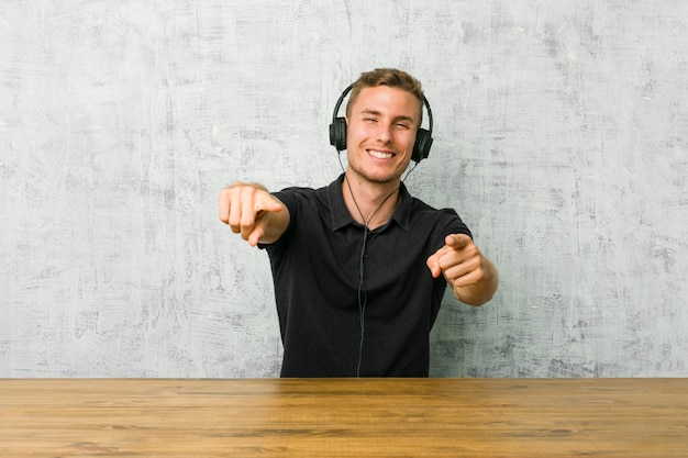 Młody kaukaski mężczyzna słuchanie muzyki w słuchawkach wesoły uśmiech wskazuje na przód.