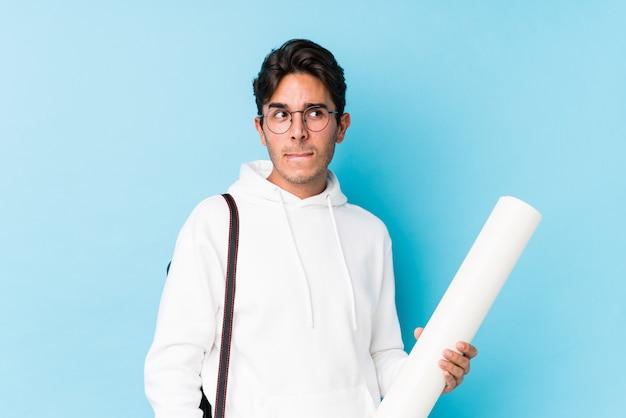 Młody kaukaski mężczyzna studiujący architekt na białym tle zdezorientowany, czuje się niepewny i niepewny.