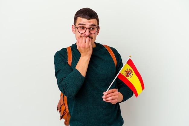 Młody kaukaski mężczyzna studiuje angielski na białym tle na białej ścianie gryzie paznokcie, jest nerwowy i bardzo niespokojny