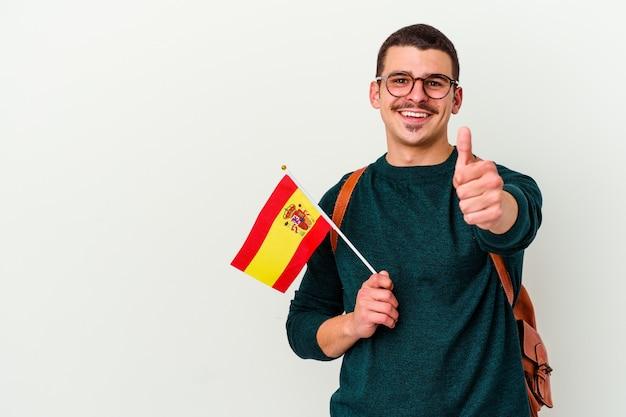Młody kaukaski mężczyzna studiuje angielski na białym tle na białej ścianie, uśmiechając się i podnosząc kciuk do góry