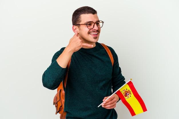 Młody kaukaski mężczyzna studiuje język angielski na białym tle, pokazując gest połączenia telefonu komórkowego z palcami.