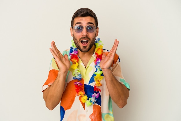 Młody kaukaski mężczyzna tańczy na hawajskiej imprezie na białej ścianie zaskoczony i zszokowany.