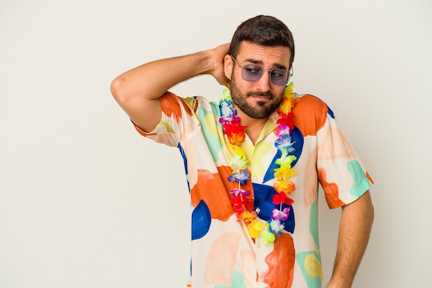 Młody kaukaski mężczyzna tańczy na hawajskiej imprezie na białym tle na białej ścianie, dotykając tyłu głowy, myśląc i dokonując wyboru.