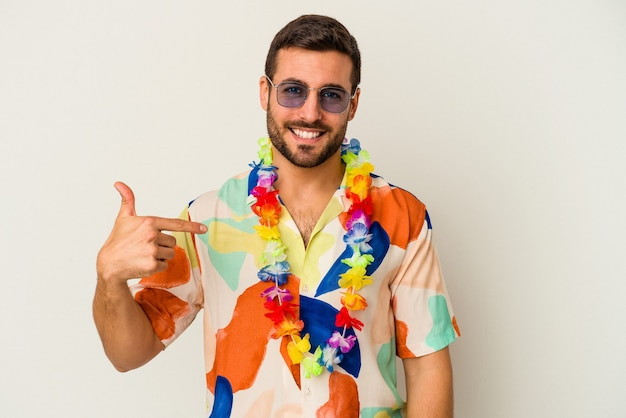 Młody kaukaski mężczyzna tańczy na hawajskiej imprezie na białym tle osoba wskazująca ręcznie na miejsce na koszulkę, dumna i pewna siebie