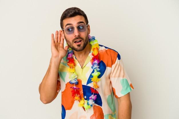 Młody kaukaski mężczyzna tańczy na hawajskiej imprezie na białym tle, próbując słuchać plotek.