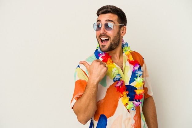 Młody kaukaski mężczyzna tańczy na imprezie hawajskiej na białym tle wskazuje palcem kciuka, śmiejąc się i beztrosko.