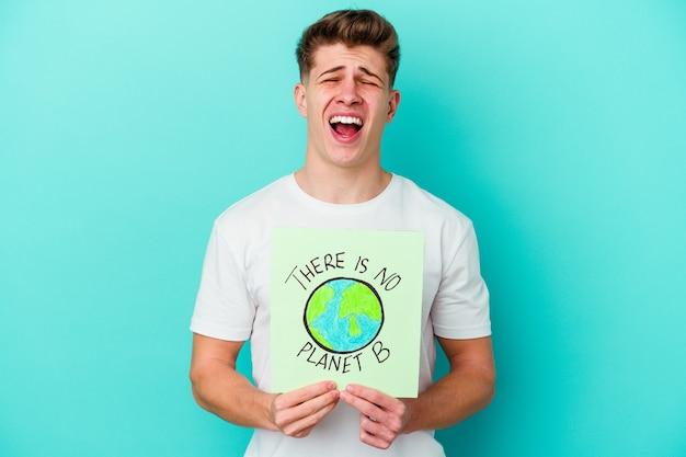 Młody kaukaski mężczyzna trzyma a nie ma tabliczki z planetą b na białym tle na niebieskim tle