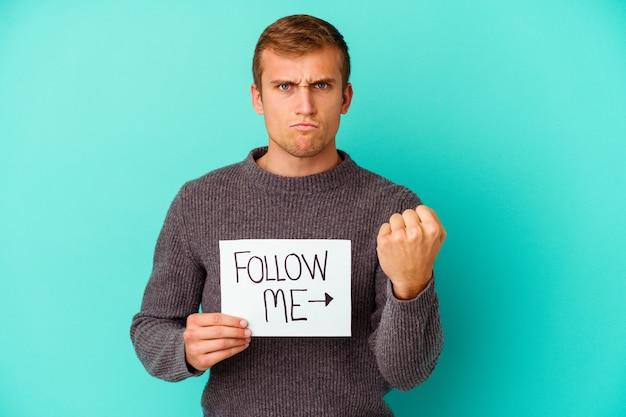 Młody kaukaski mężczyzna trzyma afisz follow me na białym tle na niebieskiej ścianie, pokazując pięść do kamery, agresywny wyraz twarzy.