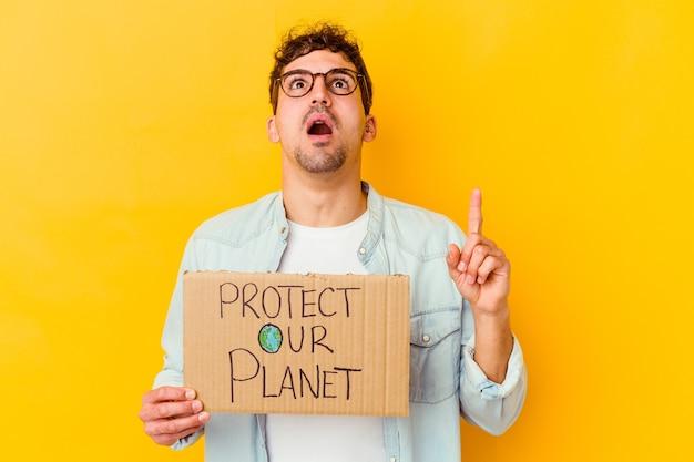 Młody kaukaski mężczyzna trzyma afisz ochrony naszej planety na białym tle, wskazując do góry z otwartymi ustami.