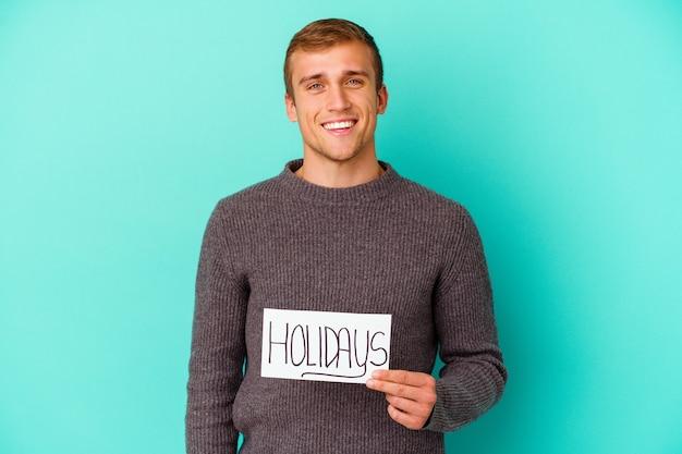 Młody kaukaski mężczyzna trzyma afisz święta na białym tle na niebieskim tle szczęśliwy, uśmiechnięty i wesoły.