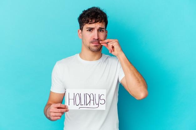 Młody kaukaski mężczyzna trzyma afisz święta na białym tle palcami na ustach, zachowując tajemnicę.