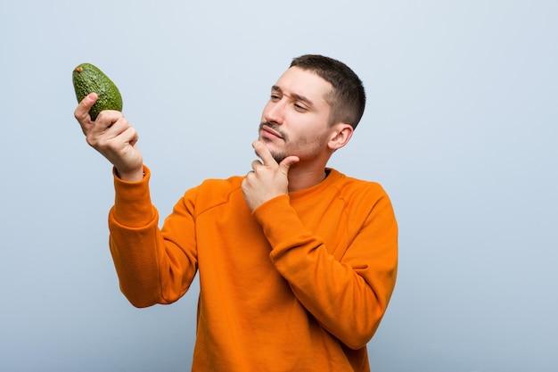 Młody kaukaski mężczyzna trzyma awokado, patrząc w bok z wątpliwym i sceptycznym wyrazem twarzy.