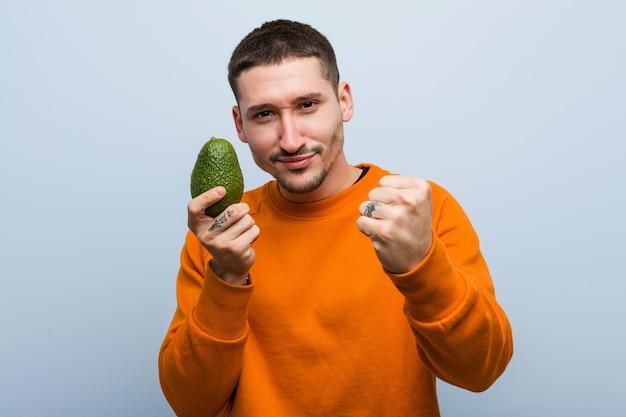 Młody kaukaski mężczyzna trzyma awokado pokazując pięść, agresywny wyraz twarzy.