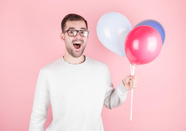 Młody kaukaski mężczyzna trzyma balony z zaskoczonym wyrazem twarzy i obchodzi urodziny na białym tle w różowej ścianie