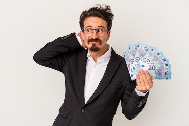Młody kaukaski mężczyzna trzyma banknoty na białym tle dotykając tyłu głowy, myśląc i dokonując wyboru.