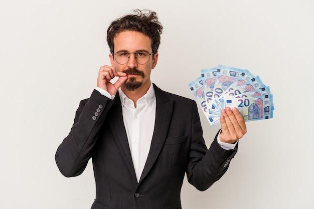 Młody kaukaski mężczyzna trzyma banknoty na białym tle na białym tle palcami na ustach, zachowując tajemnicę.