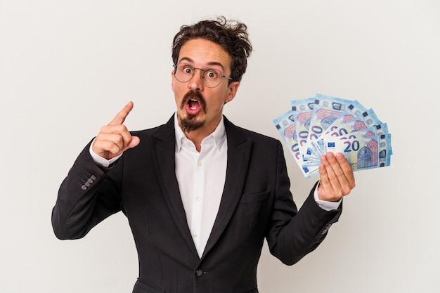 Młody kaukaski mężczyzna trzyma banknoty na białym tle na pomysł, koncepcja inspiracji.