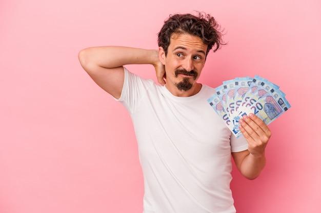 Młody kaukaski mężczyzna trzyma banknoty na białym tle na różowym tle dotykając tyłu głowy, myśląc i dokonując wyboru.