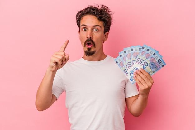 Młody kaukaski mężczyzna trzyma banknoty na białym tle na różowym tle mając pomysł, koncepcja inspiracji.
