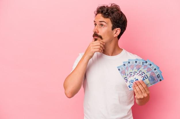 Młody kaukaski mężczyzna trzyma banknoty na białym tle na różowym tle, patrząc w bok z wyrazem wątpliwym i sceptycznym.