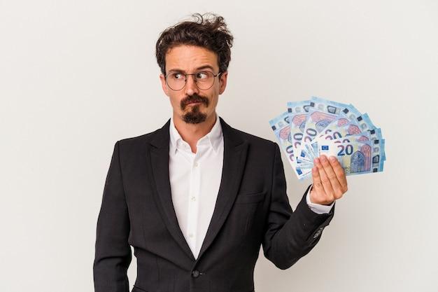 Młody kaukaski mężczyzna trzyma banknoty na białym tle zdezorientowany, czuje się wątpliwy i niepewny.