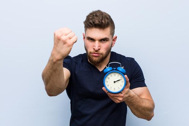 Młody kaukaski mężczyzna trzyma budzik pokazując pięść, agresywny wyraz twarzy.