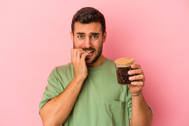 Młody kaukaski mężczyzna trzyma butelkę kawy na białym tle na różowej ścianie gryząc paznokcie, nerwowy i bardzo niespokojny.