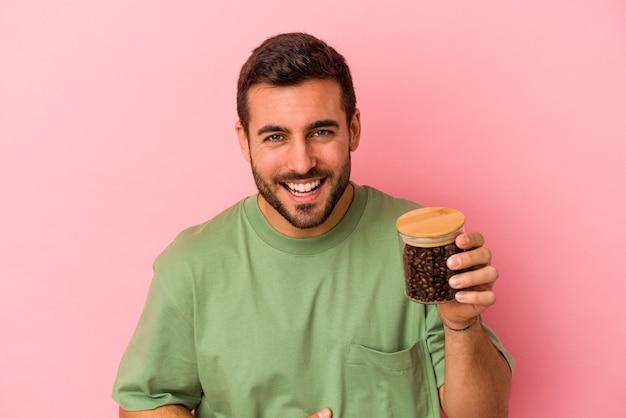 Młody kaukaski mężczyzna trzyma butelkę kawy na białym tle na różowej ścianie, śmiejąc się i dobrze się bawiąc.