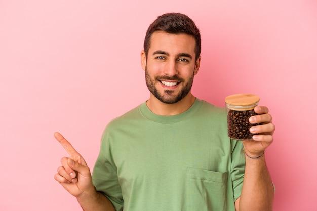 Młody kaukaski mężczyzna trzyma butelkę kawy na białym tle na różowej ścianie, uśmiechając się i wskazując na bok, pokazując coś w pustej przestrzeni