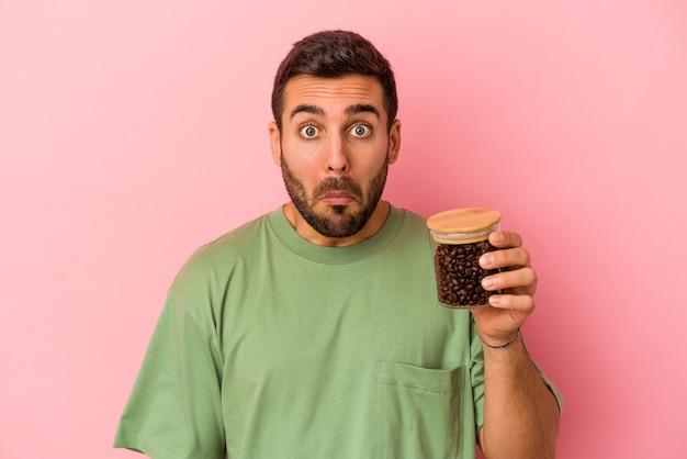 Młody kaukaski mężczyzna trzyma butelkę kawy na białym tle na różowej ścianie wzrusza ramionami i zdezorientowany otwartymi oczami.